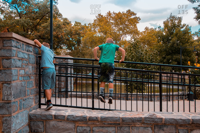 Twin Caucasian Brothers Stand and Climb Atop A Metal Handrail To Get Over A Rock Wall