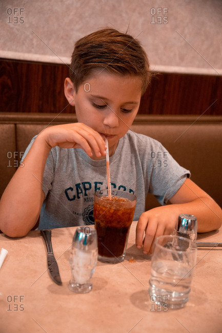A Young Caucasian Boy Drinks A Soda Through A Straw at an American Dinner