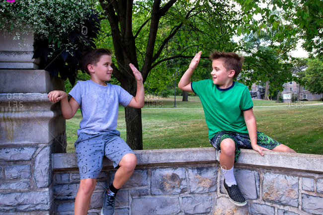 Twin Caucasian brothers Sit on top of a rock wall in a park High-Fiving One Another