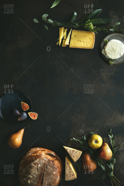 Still life scene with bread, fruits, and cheese