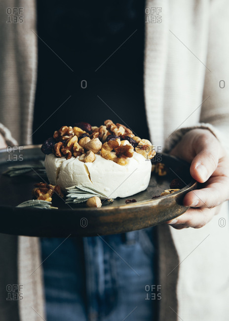 Woman holding fresh cheese with nuts