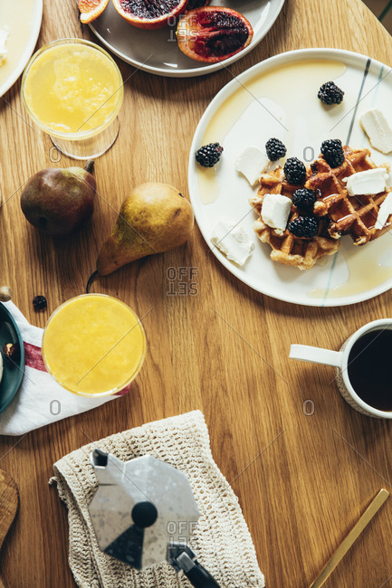 Waffles arranged with fruits, mimosas and coffee on a wooden table top