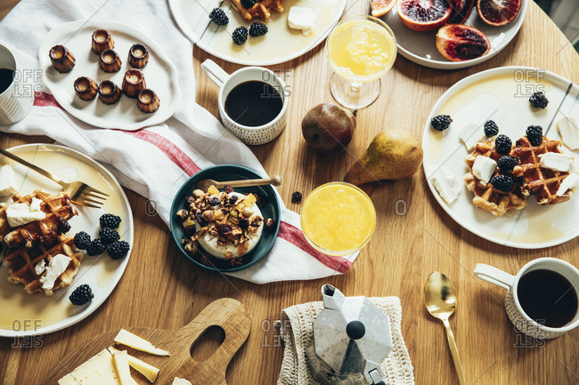 Decadent breakfast of waffles, pastries, fruit and cheese arranged on a wooden table