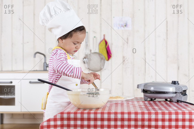 Little girl preparing waffles- wearing chef's hat