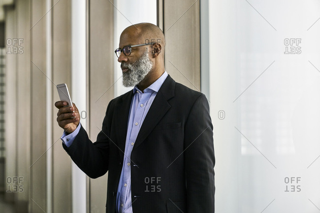 Businessman with smartphone reading messages