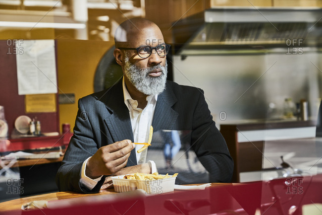 Mature businessman sitting in snack bar- eating French fries