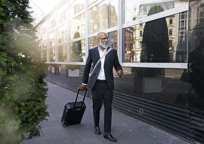 Mature businessman walking in street- pulling trolley bag