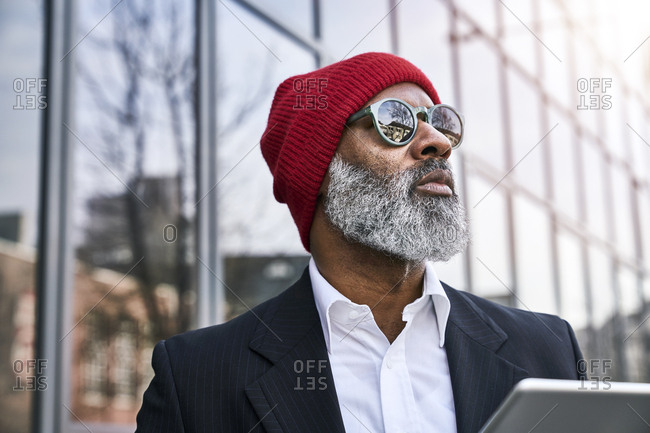 Mature businessman using digital tablet in the street