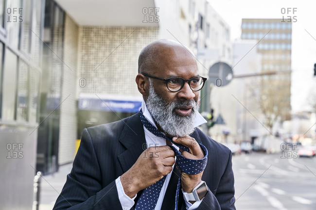 Mature businessman tying tie in the street