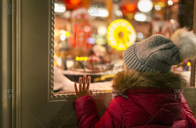 Girl looking at a Christmas shop window