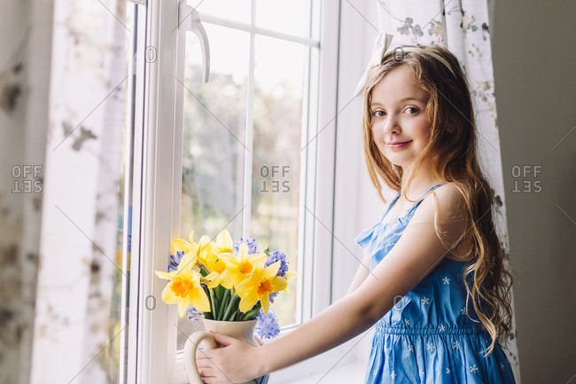 Portrait of smiling girl with flower vase of daffodils and hyacinths at home