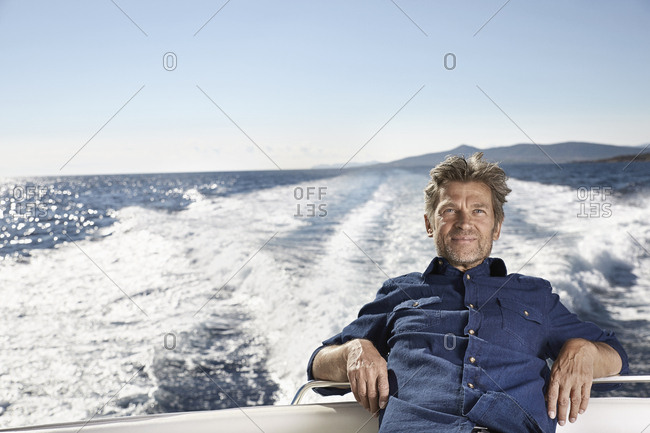 Portrait of content mature man on his motor yacht