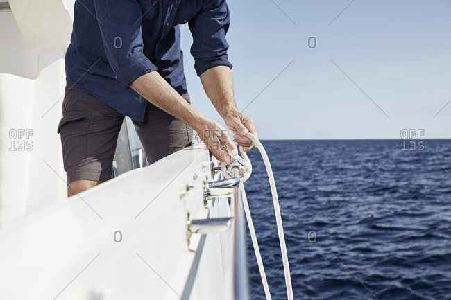 Man on motor yacht tying a knot- partial view