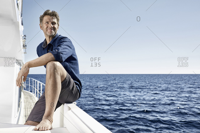 Smiling mature man on motor yacht looking at distance