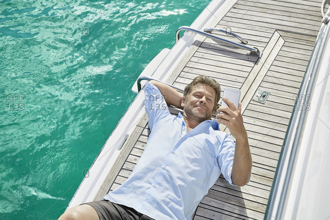 Smiling man lying on deck of his motor yacht checking emails