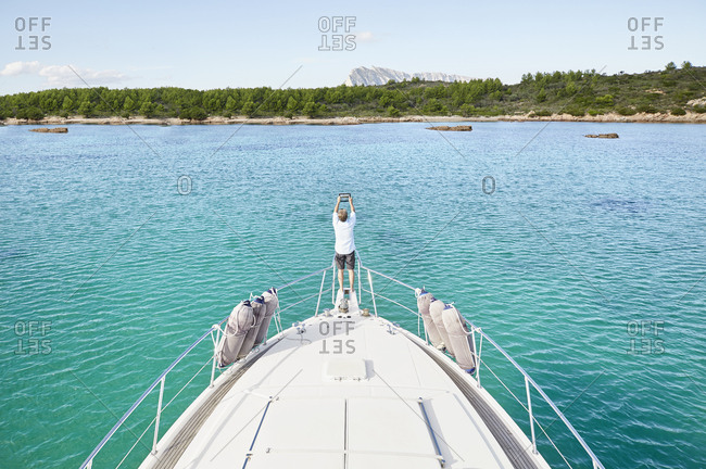 Back view of man standing at bow of his motor yacht taking picture with tablet