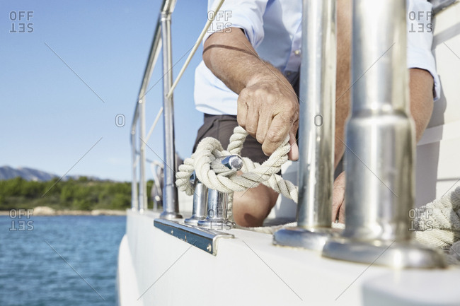 Mature man on motor yacht tying a knot- partial view