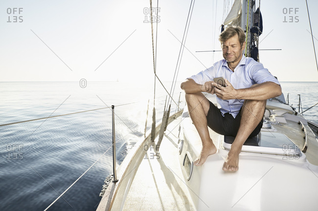 Smiling mature man sitting on his sailing boat using cell phone