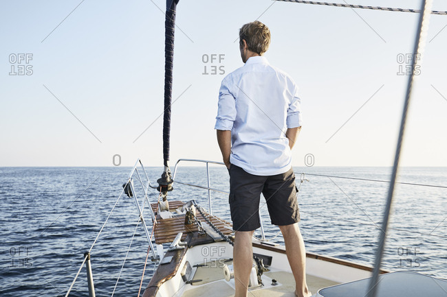 Back view of mature man standing on his sailing boat looking at distance