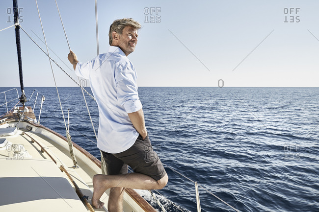 Smiling mature man standing on his sailing boat looking at distance