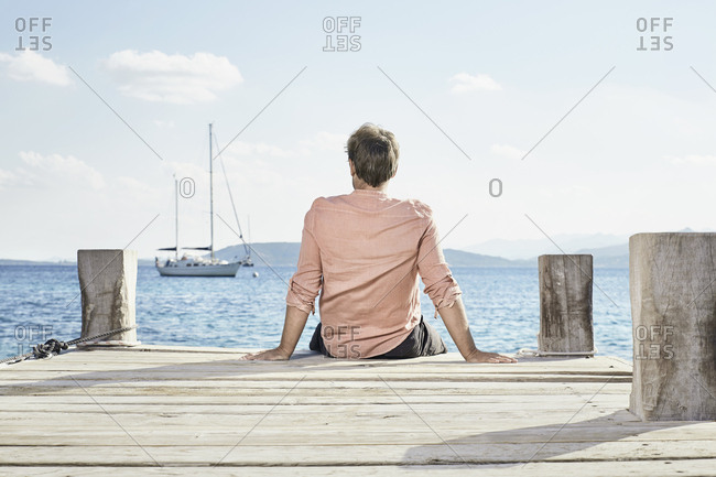 Back view of man sitting on jetty looking at distance