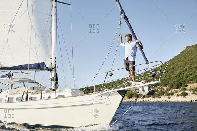 Man standing on bow of his sailing boat looking at distance