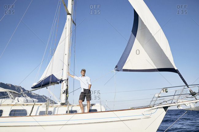 Mature man standing on his sailing boat