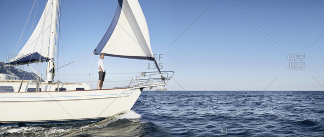 Mature man standing on his sailing boat looking at distance