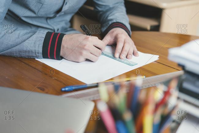 Close-up of man drafting at desk