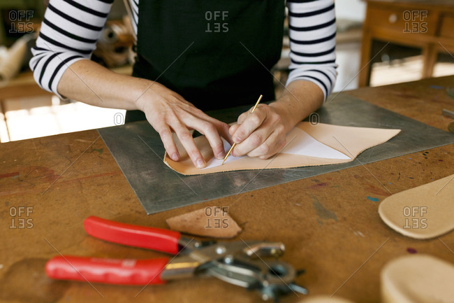 Close-up of shoemaker working on template in her workshop