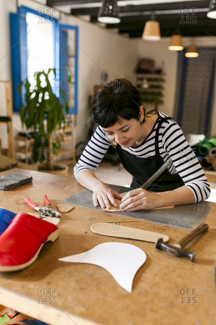 Shoemaker working on template in her workshop