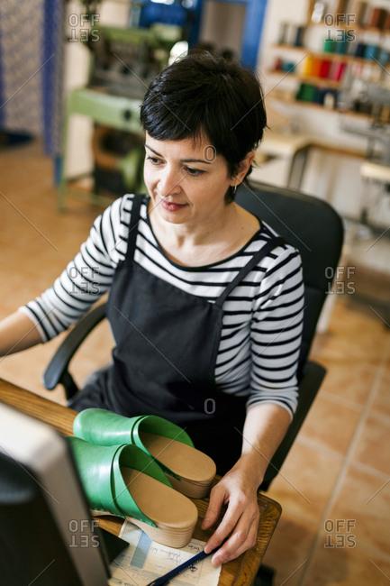 Shoemaker using computer in her workshop