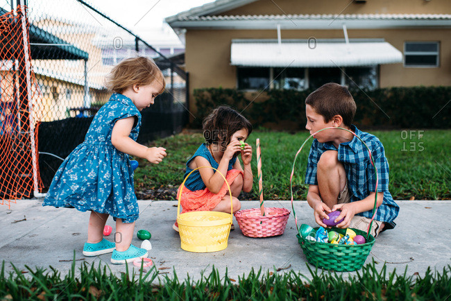 Brother and two sisters examining their Easter eggs and baskets on a sidewalk.