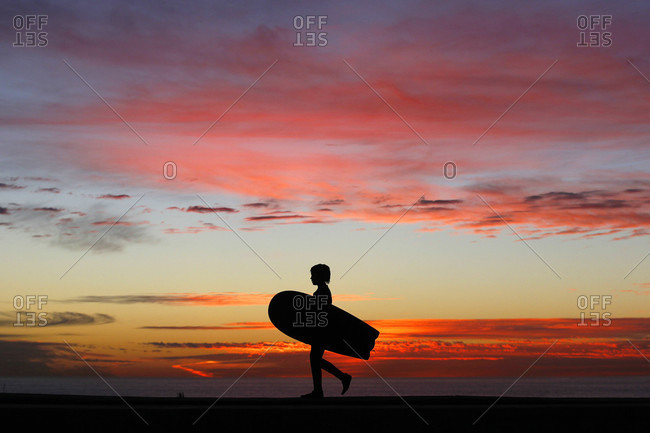 San Diego, CA, USA - January 23, 2016: A boy walks with his surfboard at sunset at Windansea Beach in the La Jolla neighborhood of San Diego, California.