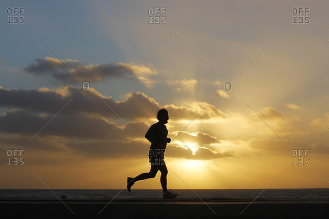 San Diego, CA, USA - January 31, 2016: A person jogs as the sun sets at Windansea Beach in the La Jolla neighborhood of San Diego, California.