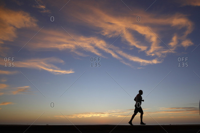 San Diego, CA, USA - January 29, 2016: A person jogs as the sun sets at Windansea Beach in the La Jolla neighborhood of San Diego, California.
