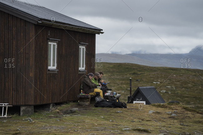 Kungsleden Trail, Lapland, Sweden - September 5, 2015: Group of hikers sit outside STF S_lka mountain hut, Kungsleden trail, Lapland, Sweden