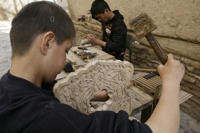 Khiva, Khiva, Uzbekistan - April 3, 2010: Uzbeki teenager carving wood at a Madrassah Khiva, Uzbekistan