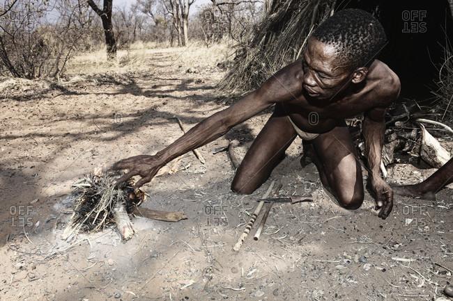 Kalahari desert, Ghanzi, Namibia - August 23, 2010: Naro bushman (San) man making a fire with commiphera sticks, Central Kalahari, Botswana