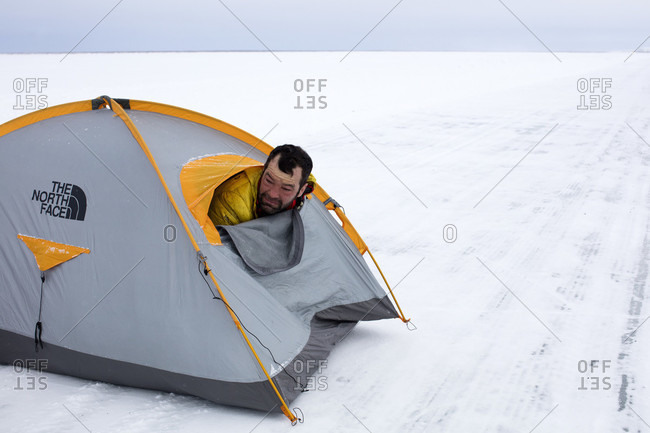 Mackenzie River Ice Road, Northwest Territories, Canada - May 29, 2015: Tiberiu Useriu, who won the non-stop self sufficient 352.64 miles (566km) 6633 Arctic Ultra foot race, awakes near the finish outside Tuktoyaktuk, Northwest Territories, Canada, March 17, 2016.
