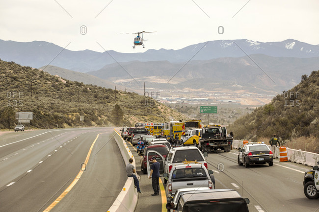 Reno, NV, USA - March 19, 2016: An emergency helicopter takes off from the scene of a traffic accident in a dry, mountainous interstate scene, with cars backed up.