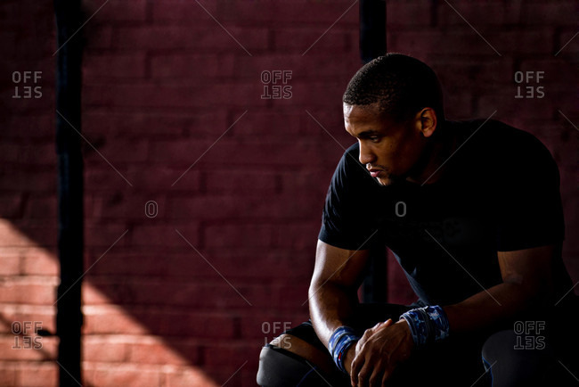 San Diego, California, USA - February 12, 2014: A man in gym outfit sits in a  gym.