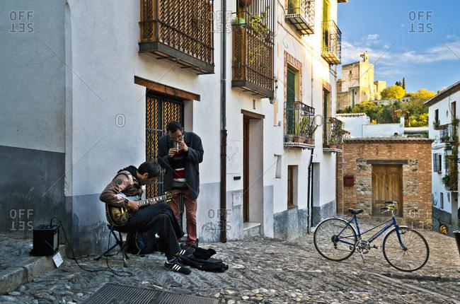 Granada, Granada, Spain - November 26, 2015: Two men playing instruments in a small square in Granada, Spain.