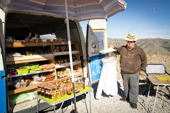 Spain, Spain, Spain - November 27, 2015: A man sells honey out of his roadside van in the mountains above Granada, Spain.