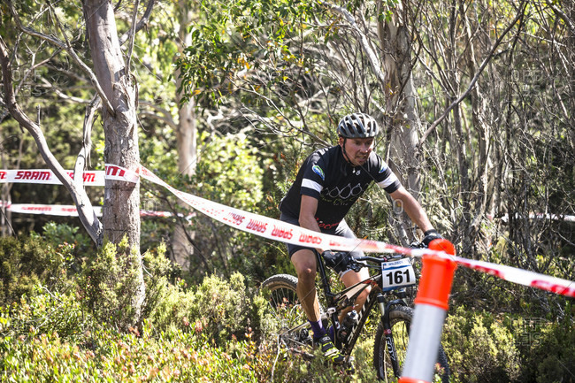 Cradle Mountain, Tasmania, Australia - January 16, 2016: Mountain bikers race the first race stage of Wildside MTB 2016, crossing Middlesex plains near Cradle Mountain.