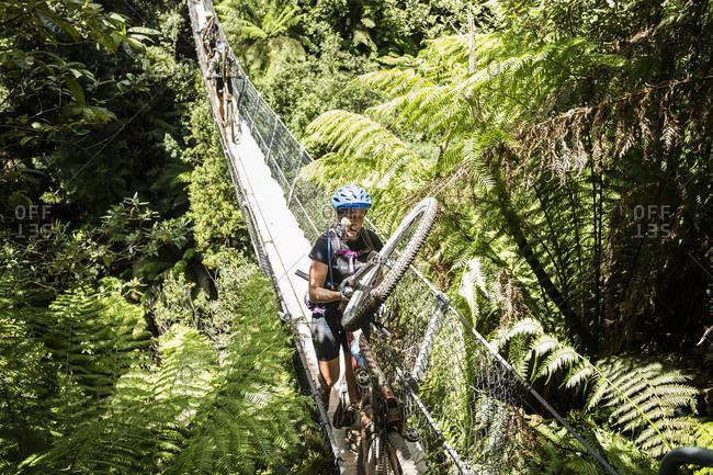 Tasmania, Tasmania, Australia - January 17, 2016: Mountain bike racers cross the Montezuma Falls suspension bridge during the 2016 Wildside MTB race in Tasmania.