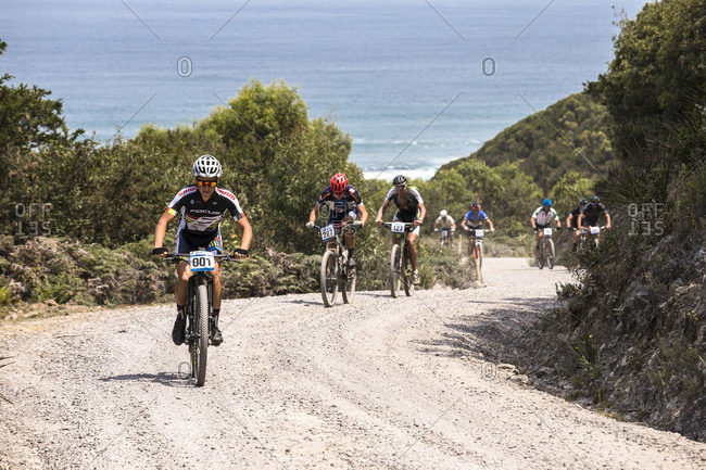Trial Harbor, Tasmania, Australia - January 18, 2016: Wildside MTB 2016 competitors climb the hill out of Trial Harbor on their way to Granville Harbor.