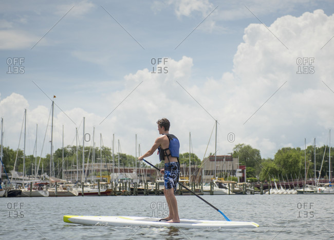 Annapolis, Maryland, United States - July 6, 2015: A young man on a stand up paddleboard on Spa Creek in Annapolis, Maryland.