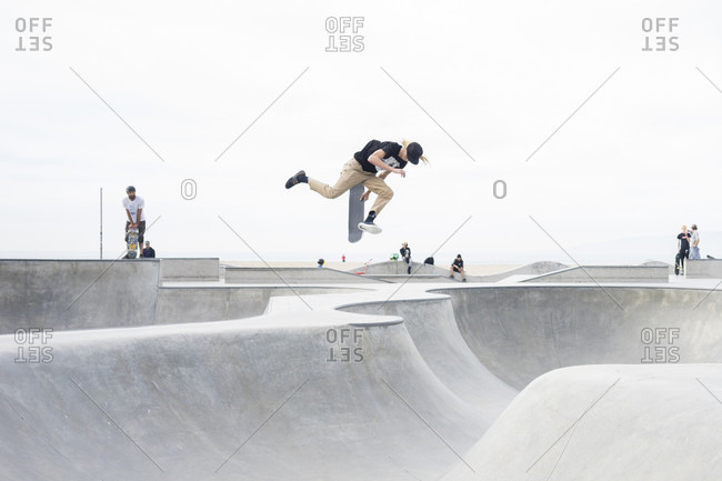 Venice Beach, Los Angeles, California, USA - January 11, 2016: Young male skateboarder tries a new trick at Venice Beach skate park, Los Angeles, California