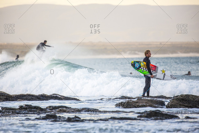 Jeffry's Bai, South Africa, South Africa - July 17, 2015: Surfer watches the waves while other surfers have fun in the background, Jeffery's Bay, South Africa